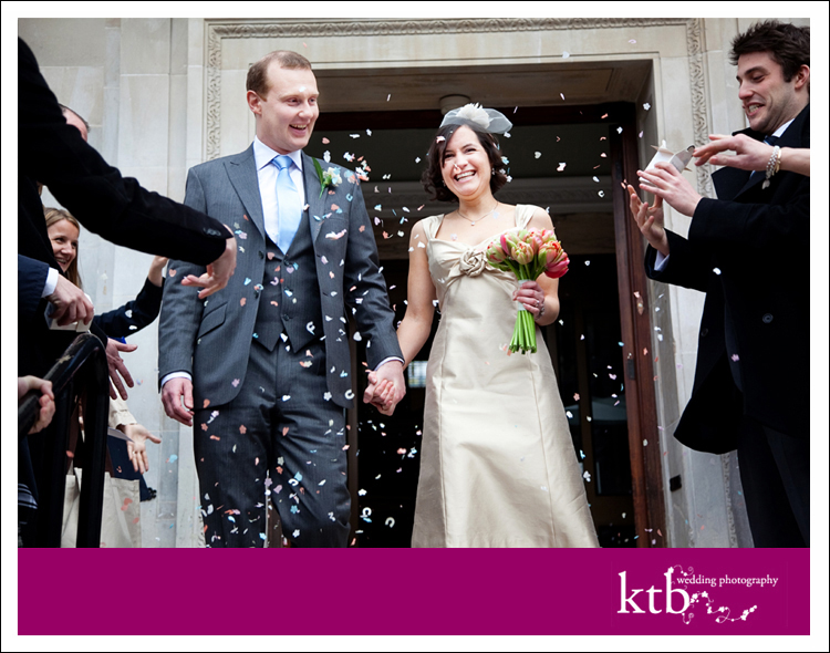 Confetti flies as the happy couple walk down the steps at Islington Town Hall.